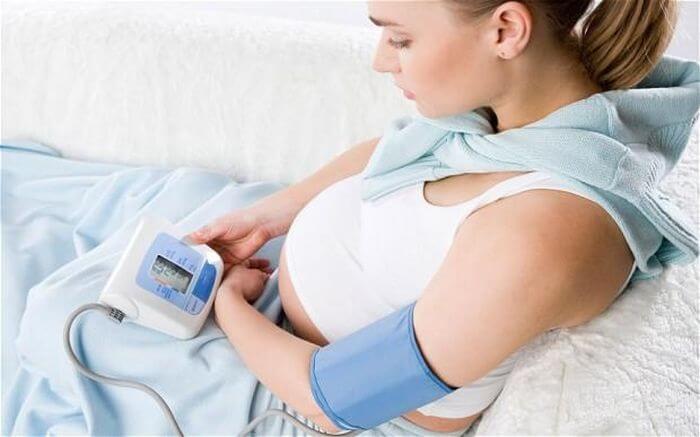 Беременная женщина измеряет давление